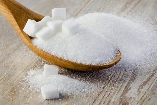 Zucker und Würfelzucker auf einem Holzlöffel.