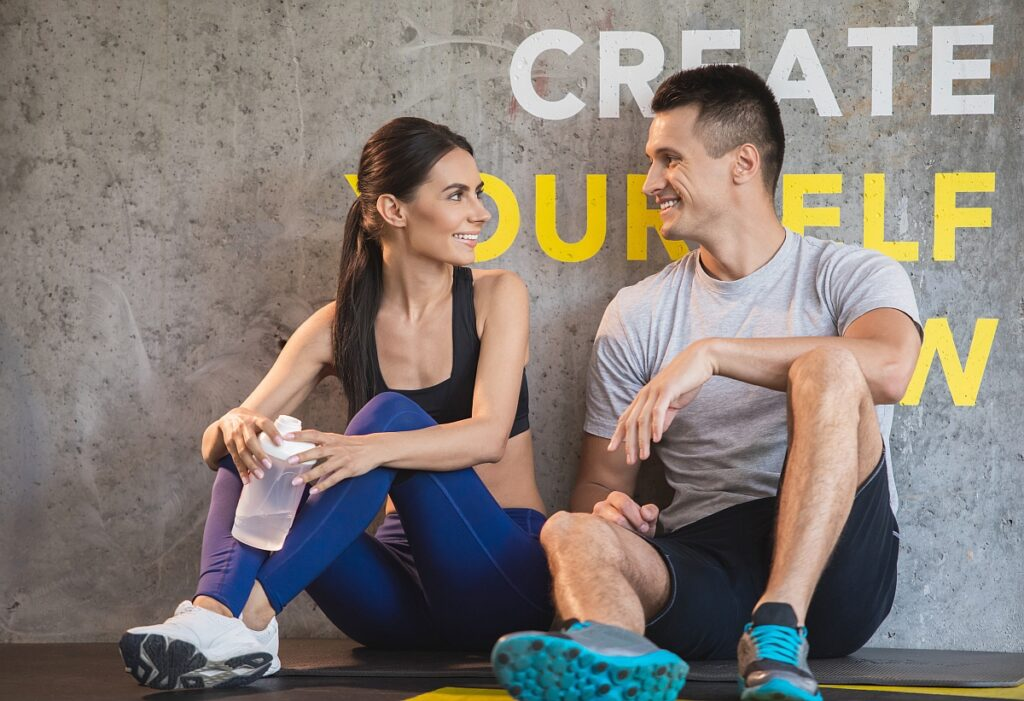Positive guy is communicating with girlfriend in gym